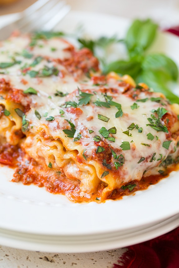 Lasagna Roll Ups on a white plate topped with basil
