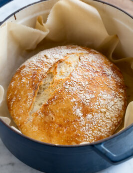 No knead bread in a large blue pot resting on parchment paper.