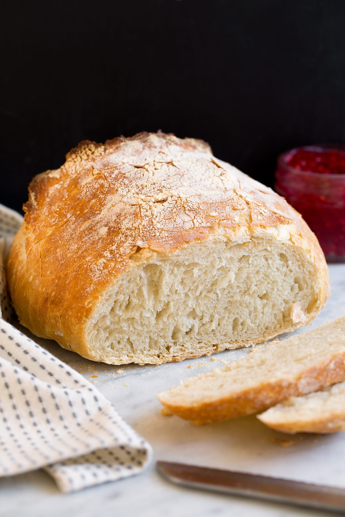No knead bread shown with a few pieces sliced of to show interior texture.