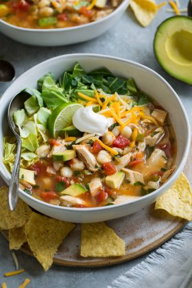 Chicken Pozole in a single serve bowl set over a plate.