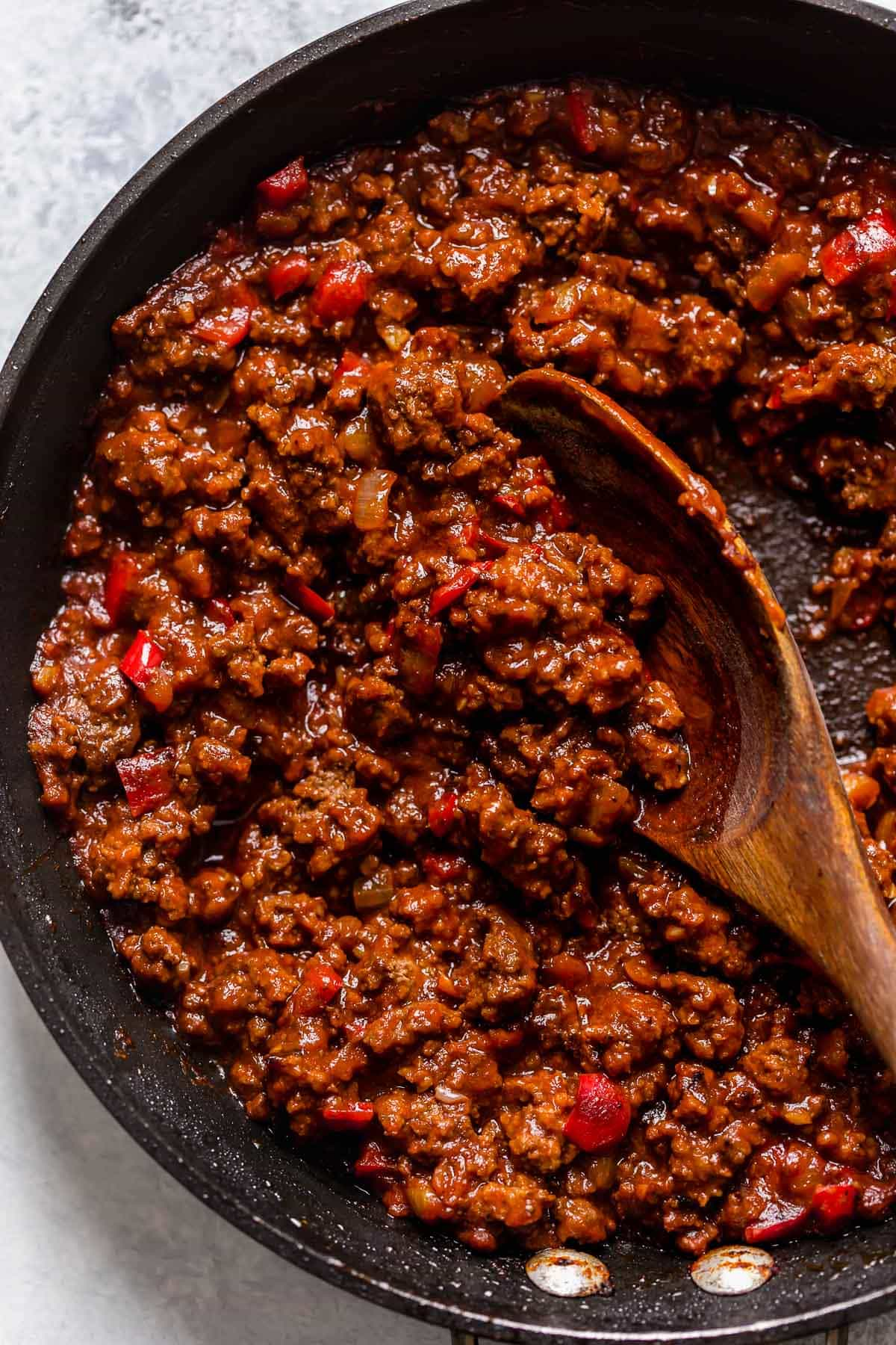 Sloppy Joe ground beef filling with sauce in a large black skillet.