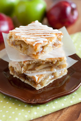 A close up of Apple pie bars stacked on a plate