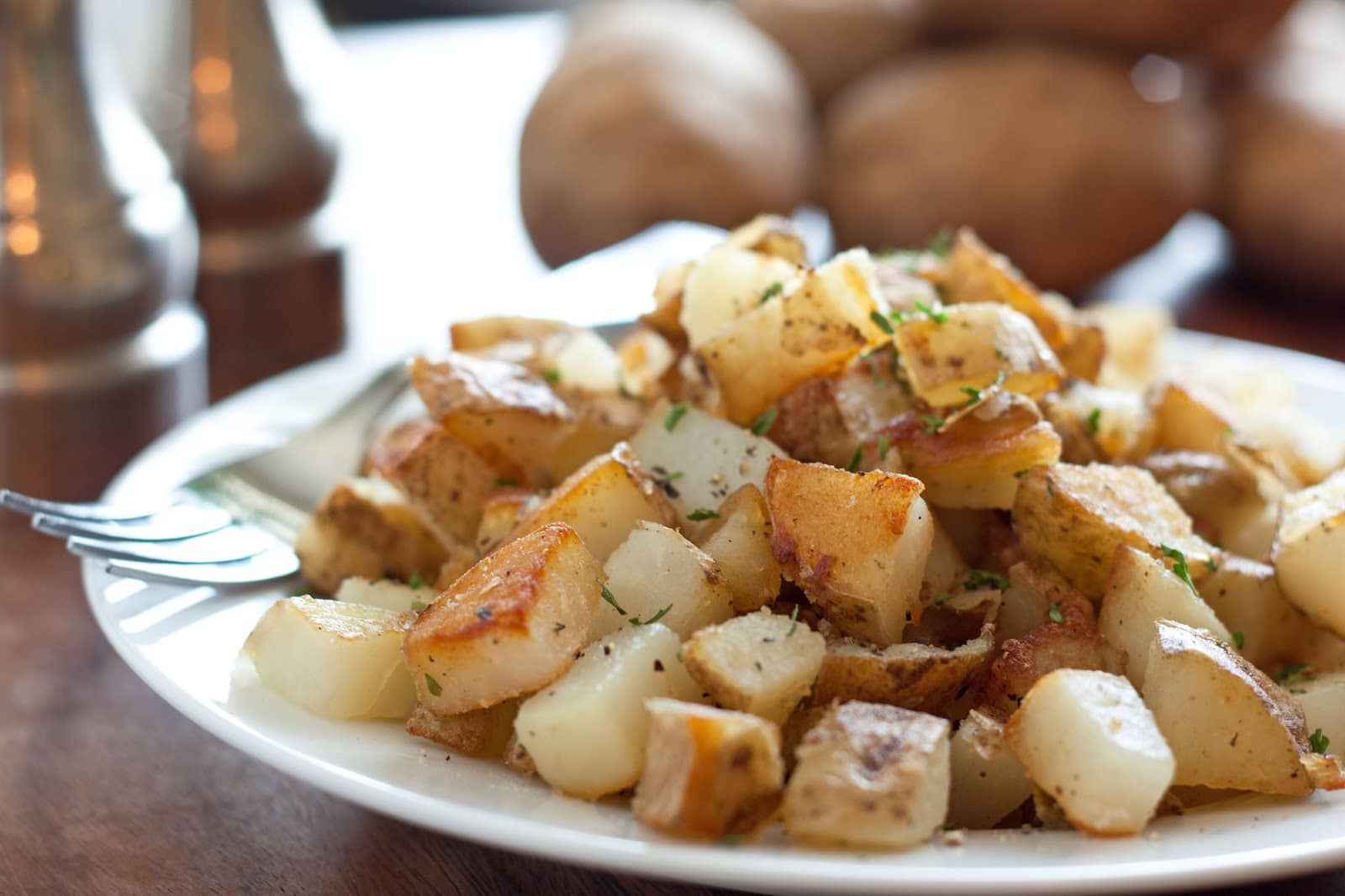breakfast potatoes perfectly browned and crisp and shown on a serving plate.