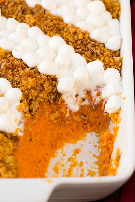 Sweet Potato in a white casserole dish. One scoop is removed to show sweet potato layer. It's topped with rows of crushed cornflakes and pecans then alternating rows of mini marshmallows.