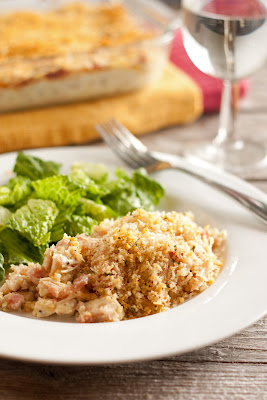 Chicken cordon bleu casserole on plate with glass of wine