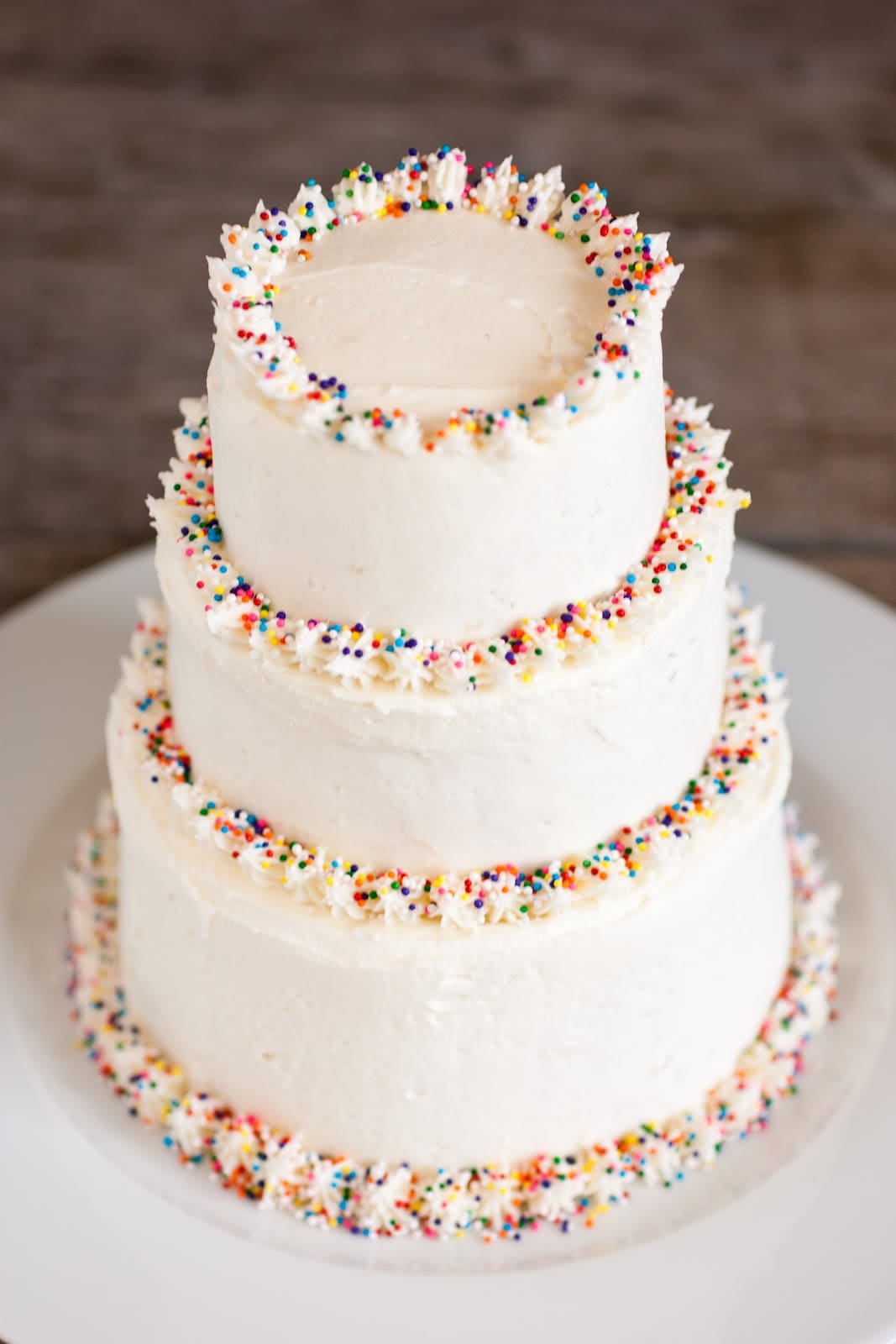 three tiered cake covered in homemade buttercream frosting