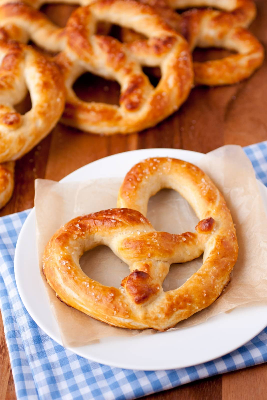 1 golden brown copycat mall pretzel shown here on a sheet of tan parchment on a blue gingham cloth set over a wood surface with 4 pretzels lying in the background