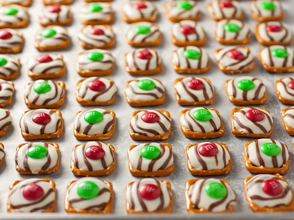 Christmas Pretzel M&M Hugs lying on a baking sheet