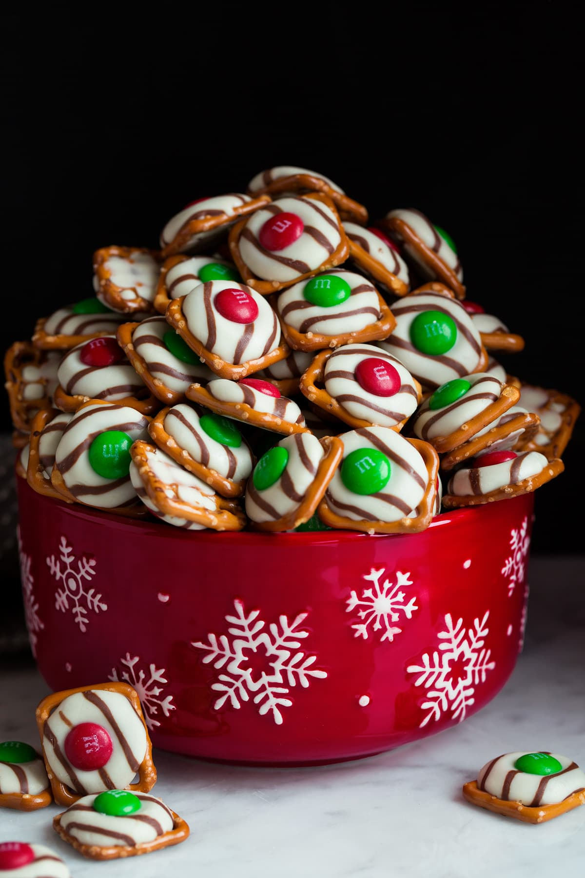Pretzel M&M Hugs in a red snowflake bowl. The consist of square pretzel base, hug chocolate and red and green M&M's.