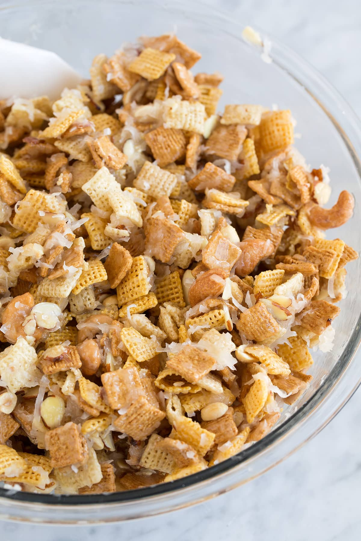 Sweet and sticky chex mix in a glass mixing bowl set over a marble surface. It includes corn and rice chex cereal, golden grahams, nuts, coconut and a butter sugar topping.