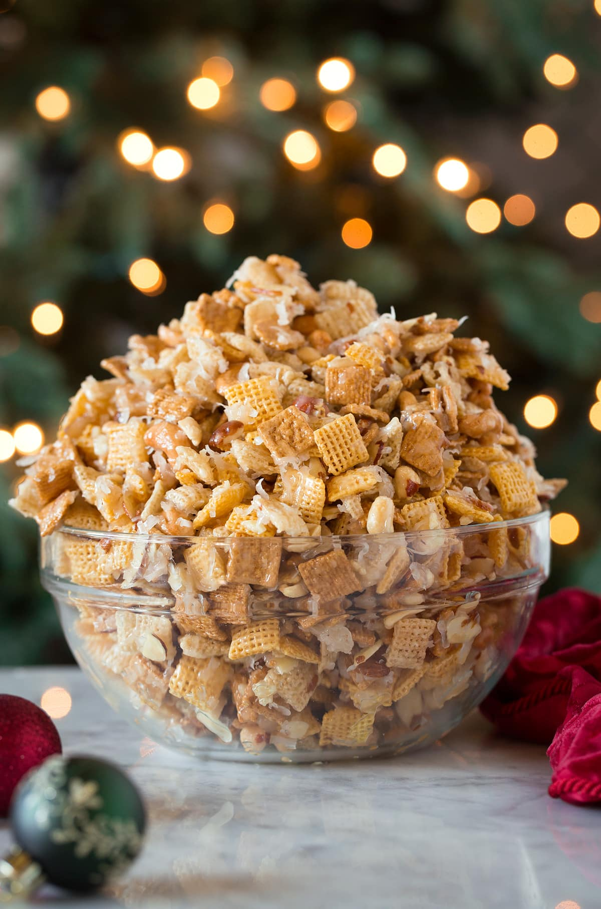 Sweet Chex Mix in front of a Christmas tree in a glass bowl.