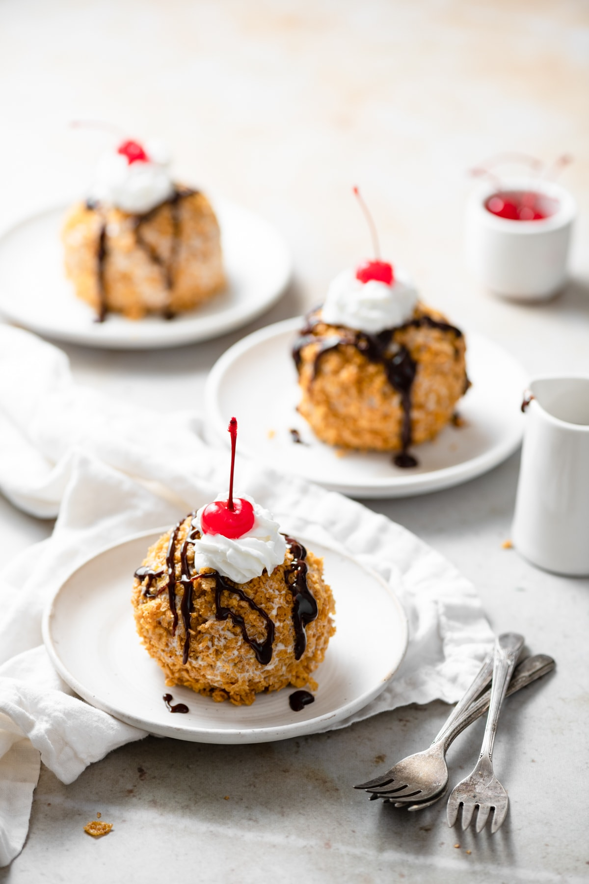 Three individual servings of fried ice cream coated in cinnamon cornflake topping, drizzled with chocolate sauce and garnished with a cherry.