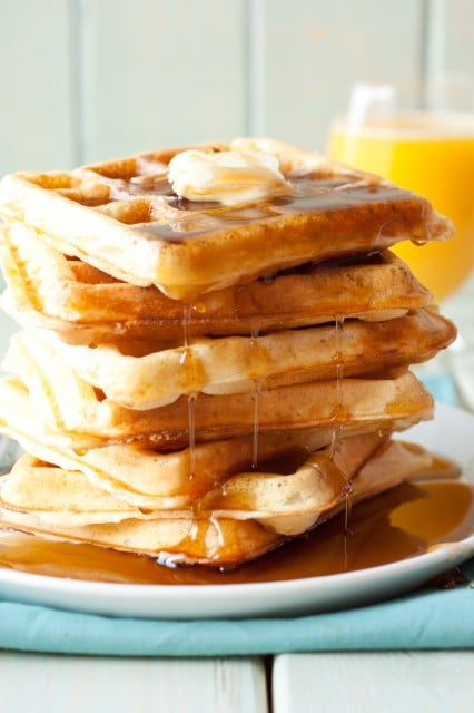 Stack of homemade buttermilk waffles drenched in maple syrup