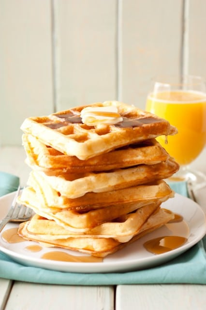 Stacked buttermilk waffles hot off the iron with butter and syrup
