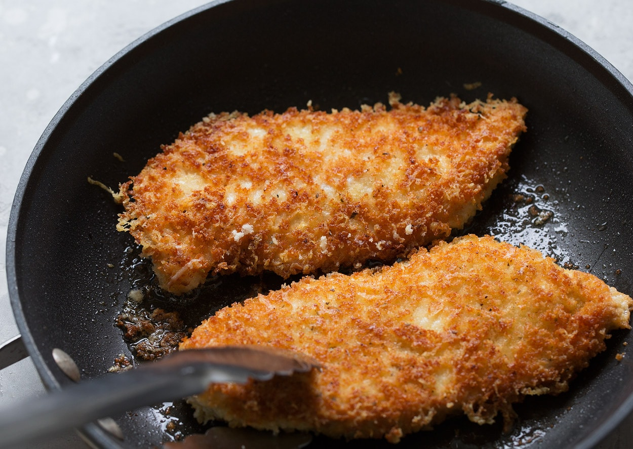 Searing chicken parmesan pieces in olive oil in black non-stick skillet until golden brown.