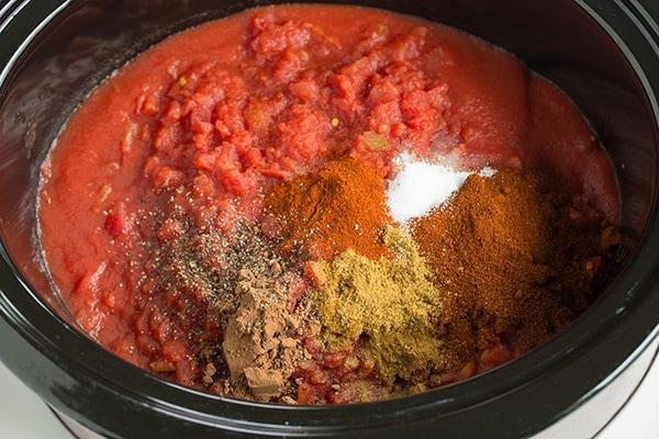 Tomatoes and spices in a slow cooker to make slow cooker chili