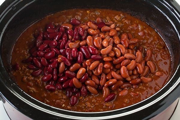 Beans being added to slow cooker chili