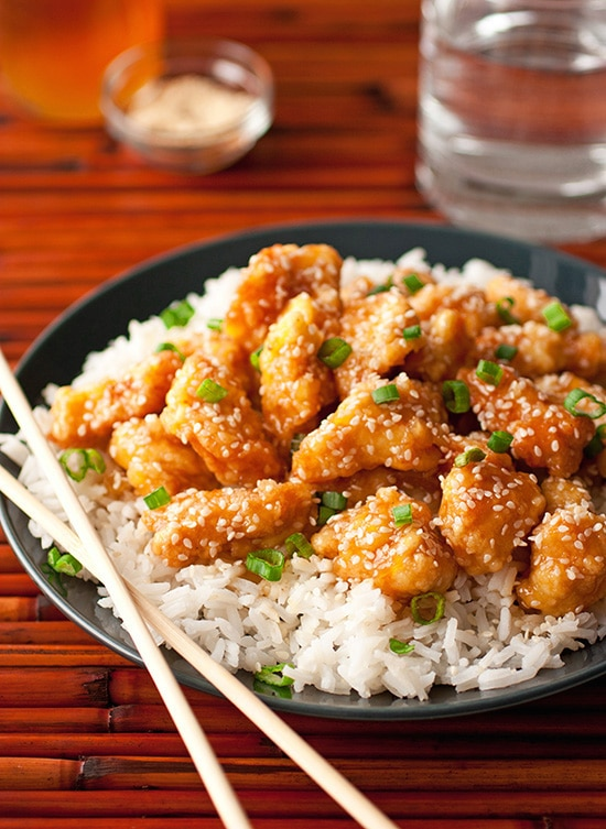 Honey Sesame Chicken atop bed of white rice with chopsticks