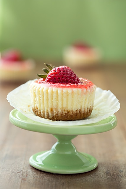 cheesecake cupcakes topped with a strawberry on a cake stand