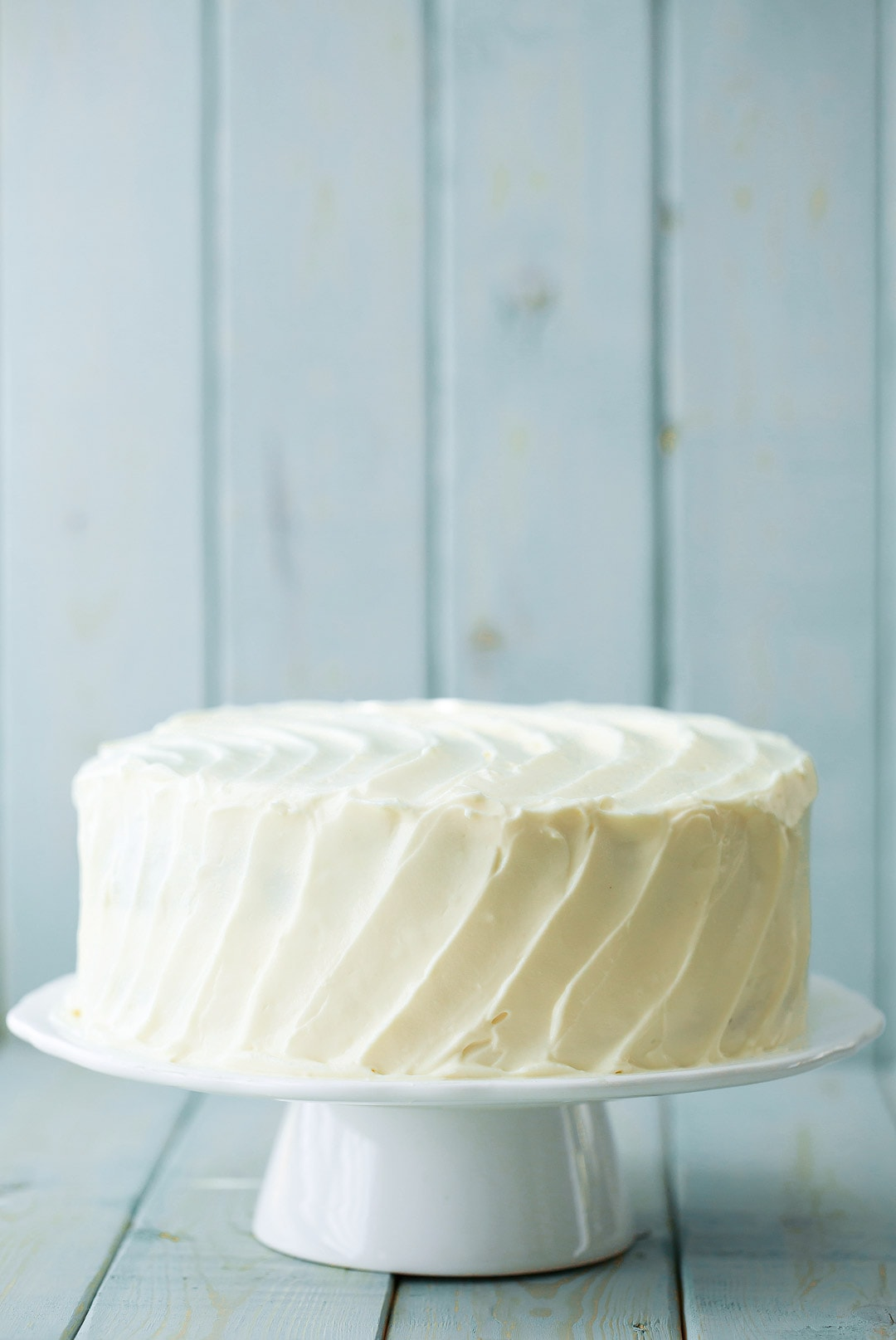Banana Cake with cream cheese frosting on a white cake stand