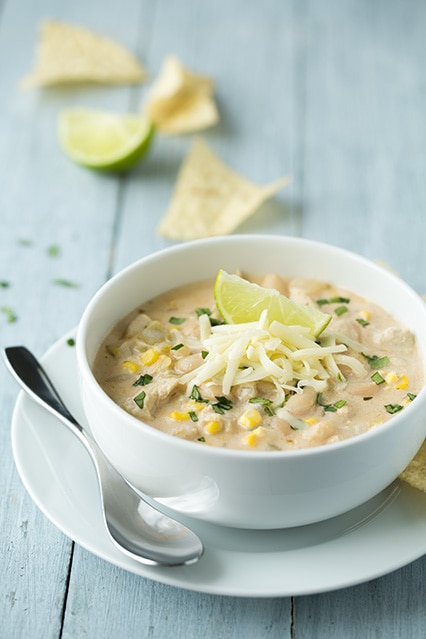 Creamy white bean chicken chili in bowl with lime and cheese