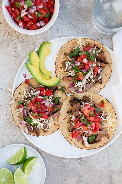 Carne Asada Tacos plated with avocado and pico de gallo