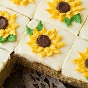 Zucchini Cake with Cream Cheese Frosting in a baking dish cut into slices. Each slice is decorated with a yellow piped buttercream sunflower.