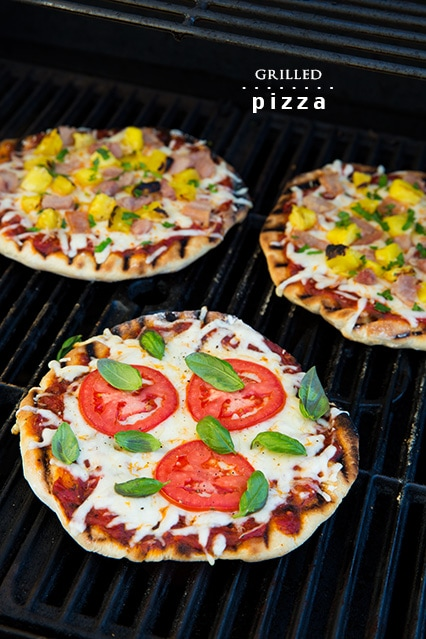 three grilled pizzas on grill
