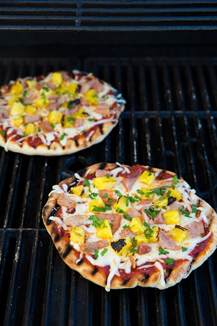 two grilled pizzas on grill