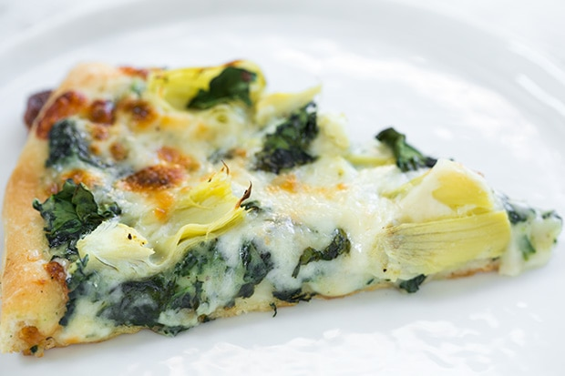 cheesy Artichoke pizza slice on white plate
