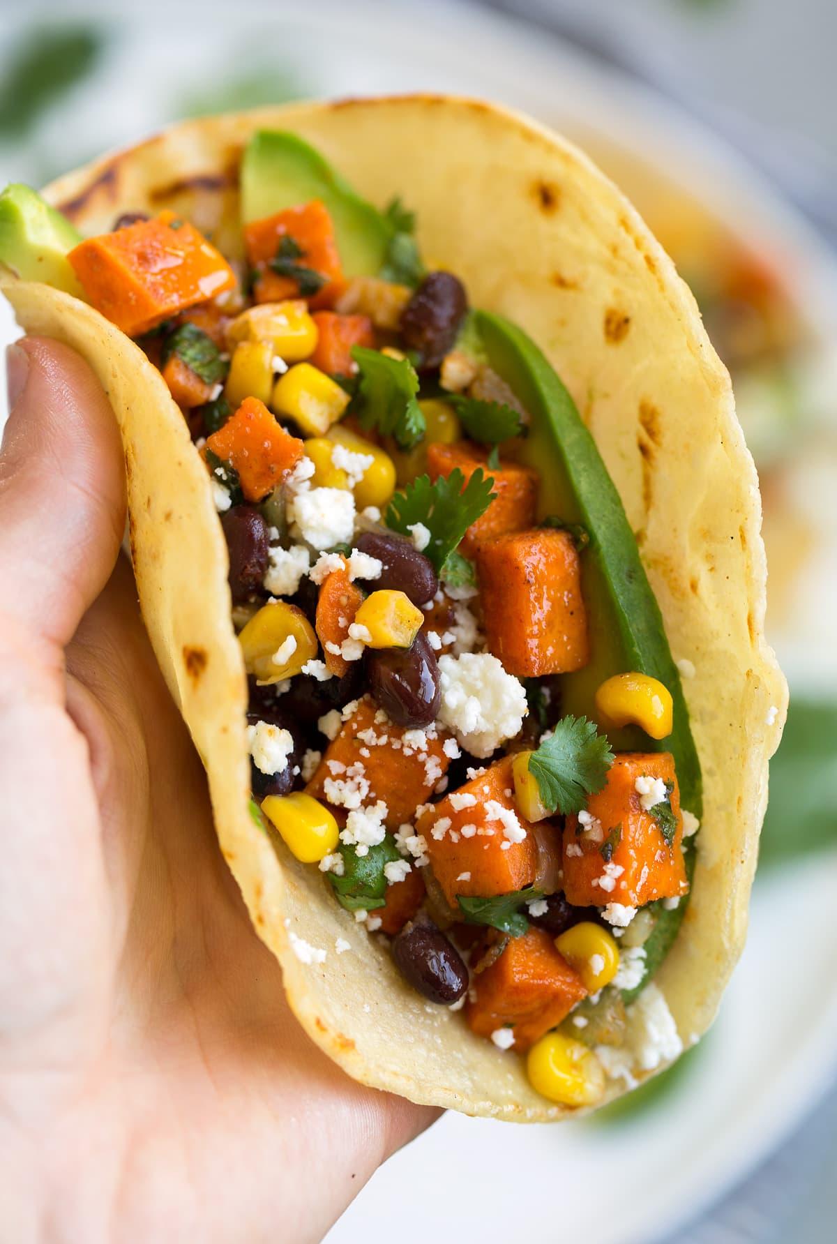 Close up image of vegetarian filled sweet potato, black bean and avocado taco.