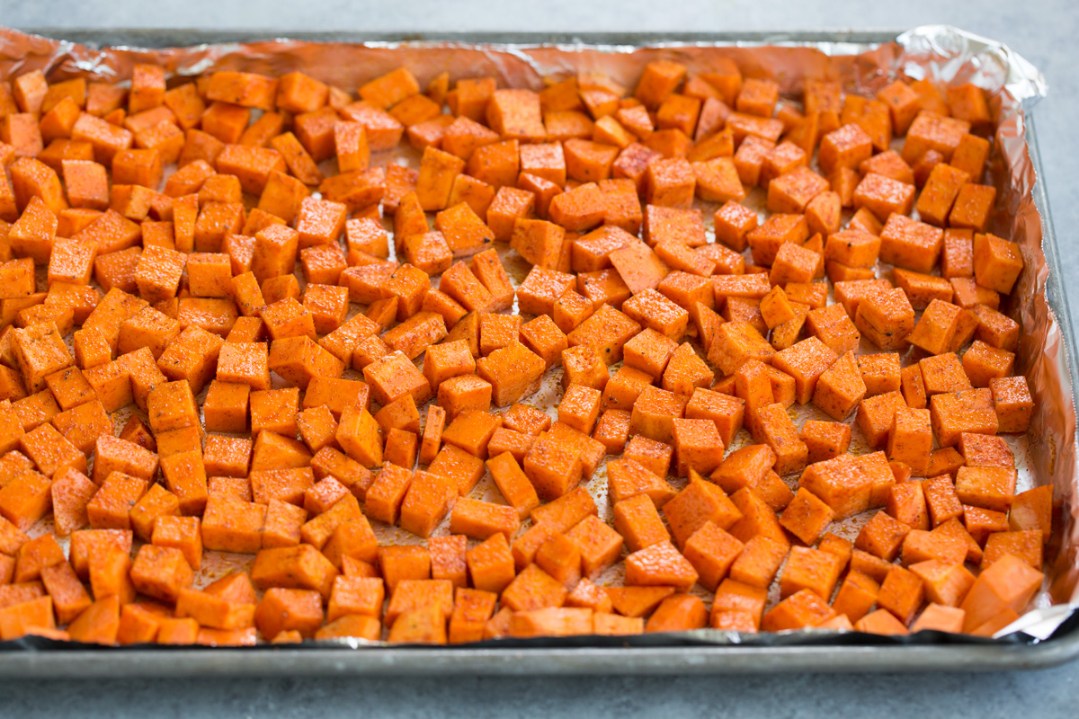 Diced, spiced sweet potatoes on baking sheet before roasting in oven.