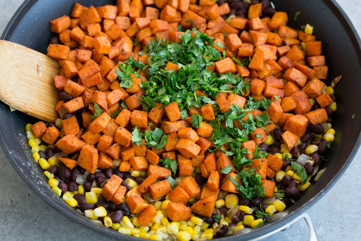 Adding sweet potatoes cilantro to skillet