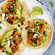 Three sweet potato and black bean tacos on white plate.