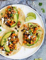 Three sweet potato and black bean tacos on white plate.