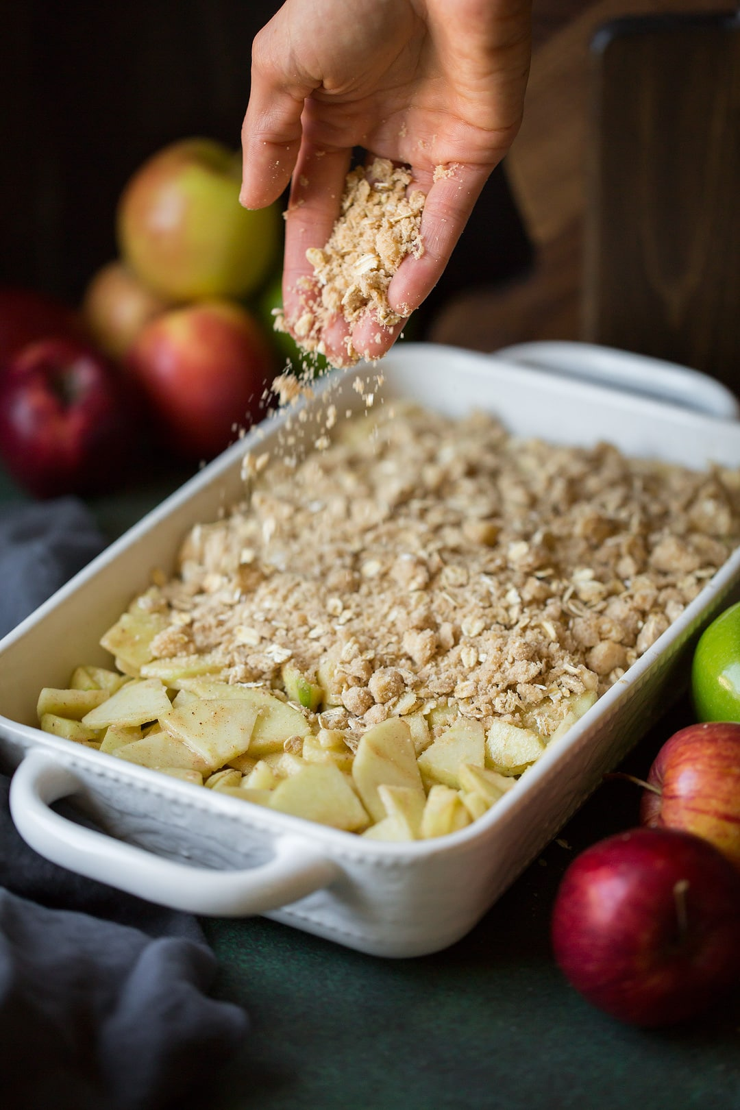 sprinkling apple crisp topping onto sliced apples