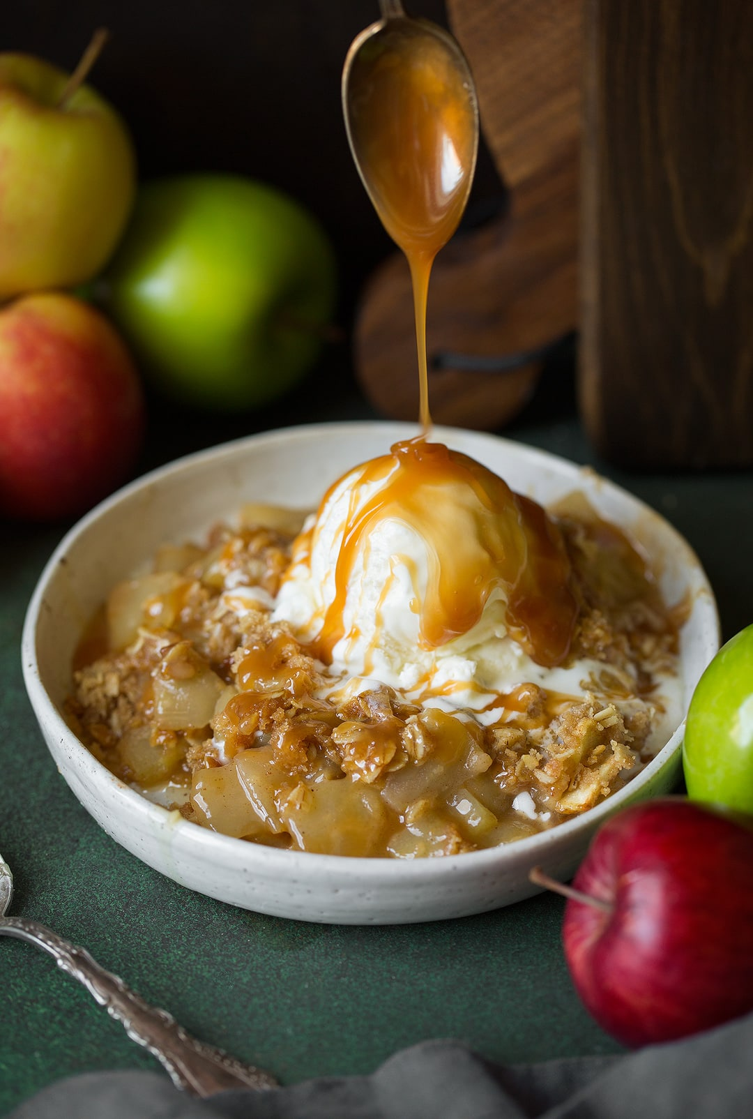 Drizzling caramel sauce onto a bowl of apple crisp and scoop of ice cream