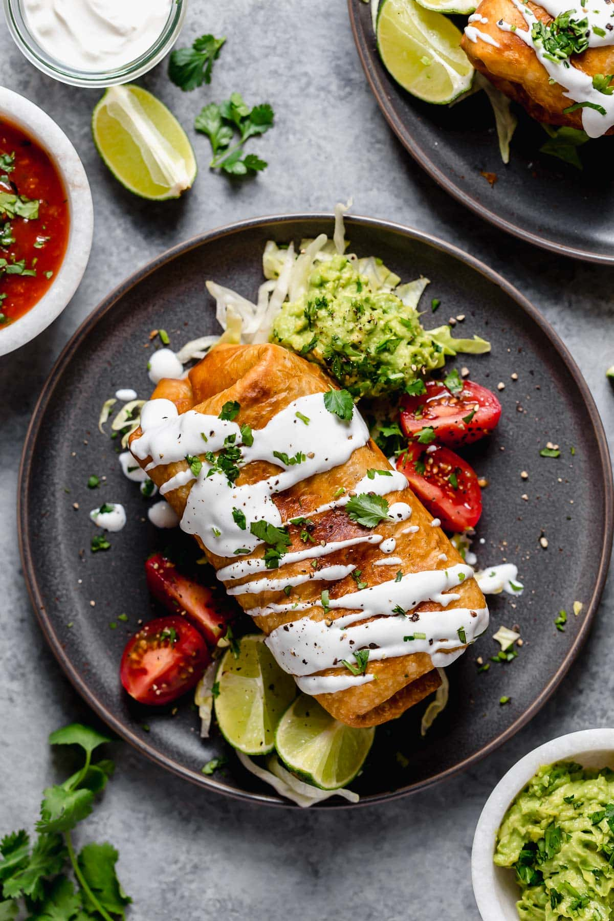 Chimichanga on a dark plate garnished with guacamole, sour cream, tomatoes and cilantro.