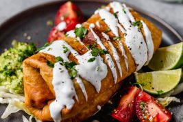 Chicken Chimichanga on a plate. It's drizzled with sour cream, garnished with cilantro and served with tomatoes and guacamole on the side.