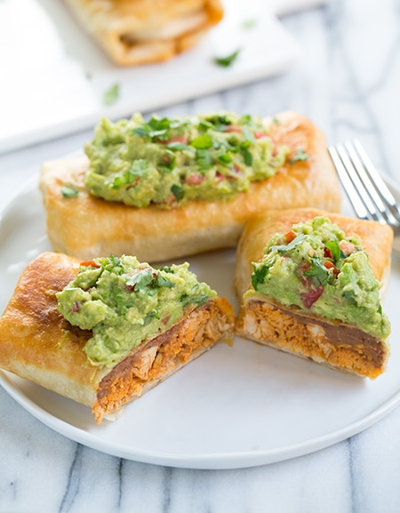 Chicken Chimichangas sliced in half on plate with guacamole on top