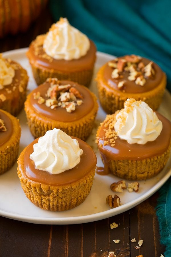 Mini Pumpkin Cheesecakes with Salted Caramel Sauce on a white serving plate.