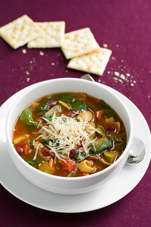 Olive Garden Minestrone Soup in a white bowl topped with cheese