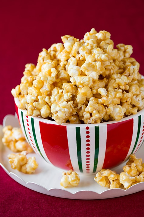 Mound of caramel popcorn in a serving bowl over a white platter.