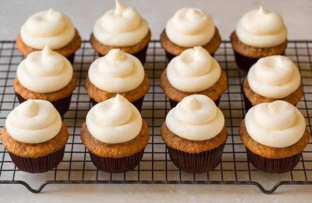 Adding cream cheese frosting to carrot cake cupcakes.