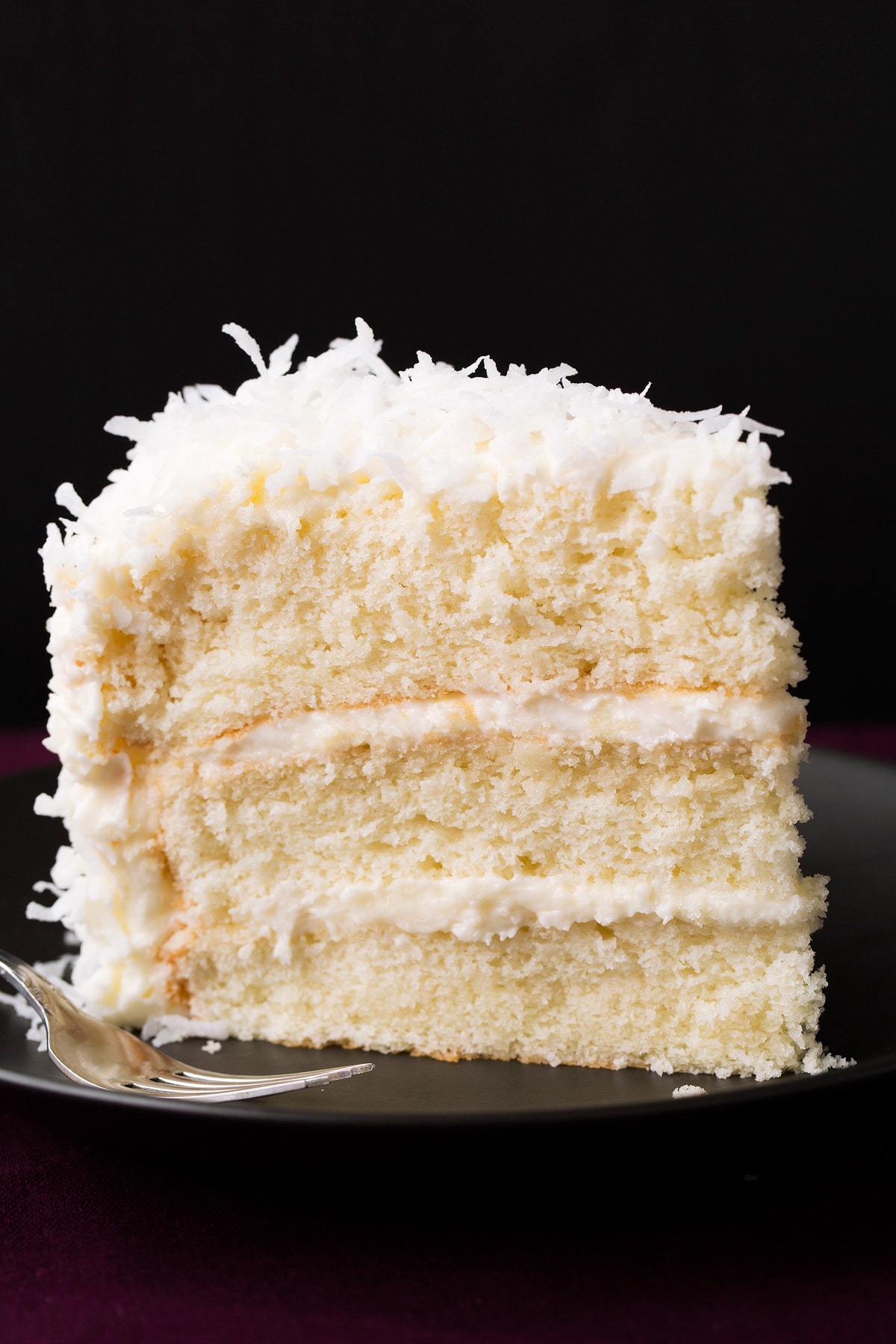 Slice of three layered homemade coconut cake on a black plate with a black background.