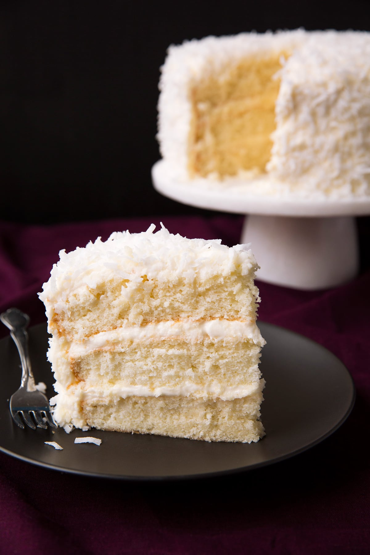 Single slice of easy coconut cake with a remainder of cake in the background.
