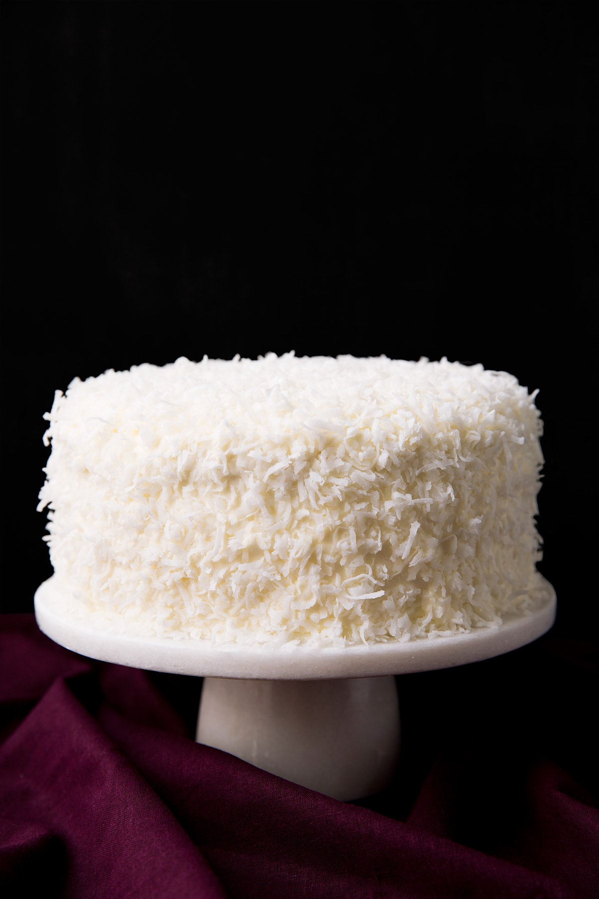 Whole made from scratch coconut cake garnished with lots of coconut and set over a white marble cake stand with a black ground and a maroon tablecloth underneath.