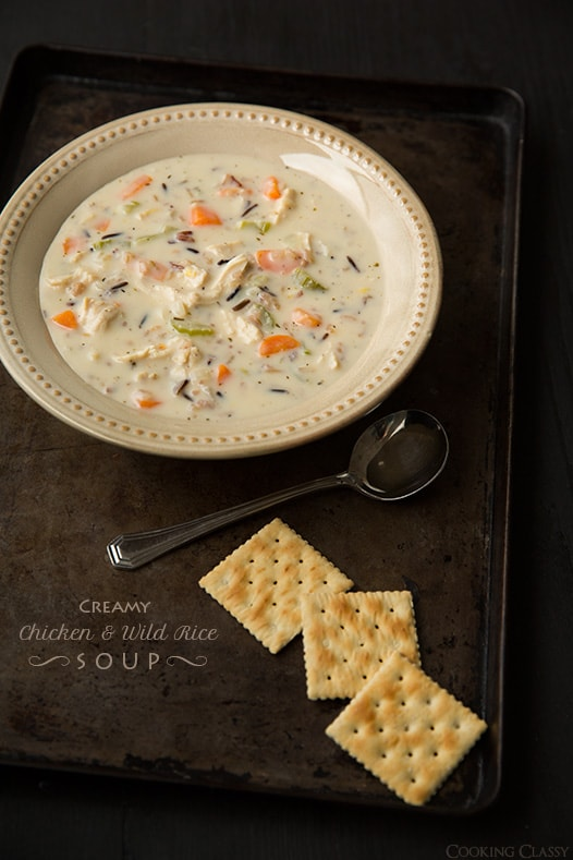 A bowl of Creamy Chicken Wild Rice Soup with three crackers at the side and a spoon