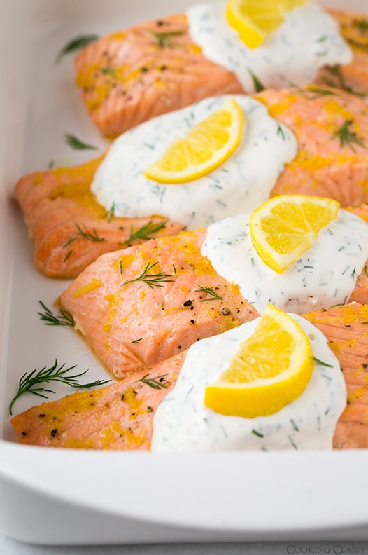 close up of lemon salmon garnished with yogurt sauce and lemon slices in baking dish