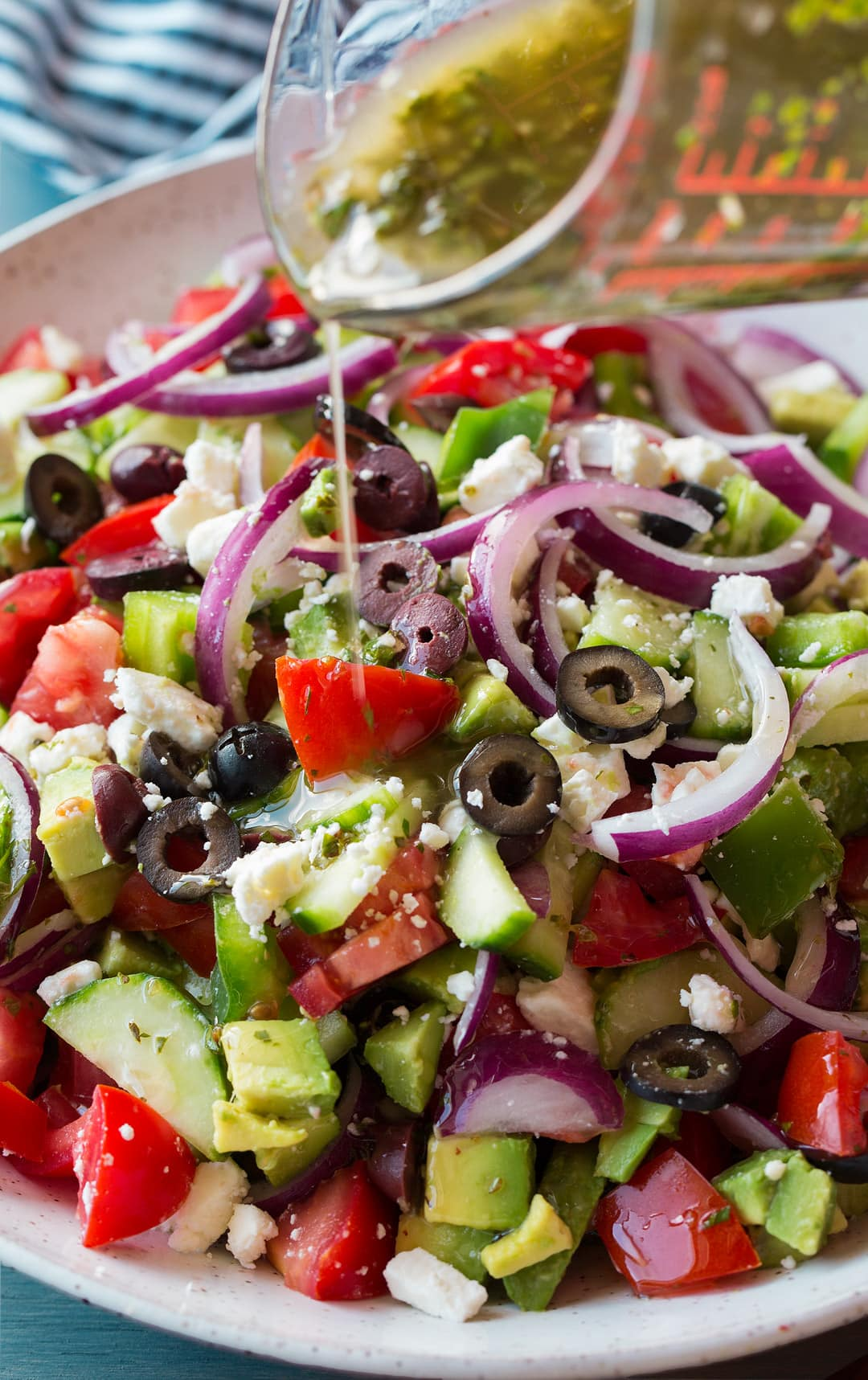 Greek Salad in a bowl with dressing getting poured over